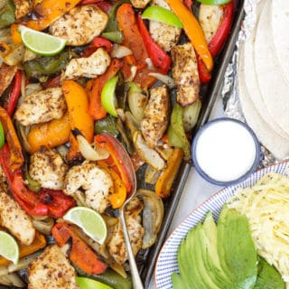 Tray of oven baked chicken fajitas with peppers, lime wedges, tortillas in foil, yoghurt, avocado and grated cheese on a blue striped plate.
