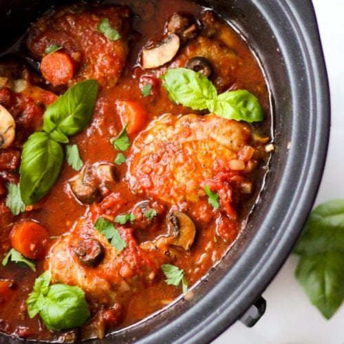 Slow cooker chicken cacciatore in slow cooker sprinkled with basil