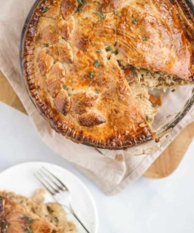 Chicken pie recipe from overhead with slice cut out on wooden board.