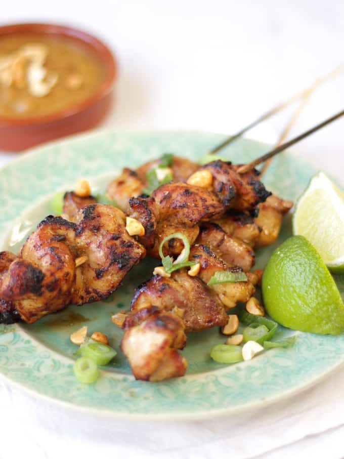 Side view of chicken satay skewers and peanut sauce with limes.