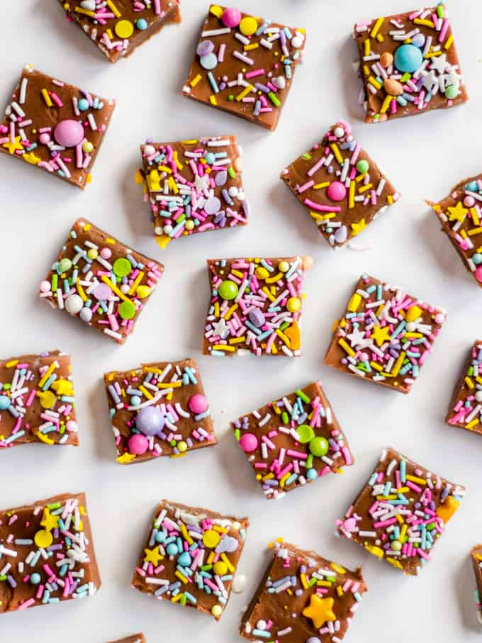 Cubes of chocolate microwave fudge with colourful sprinkles on a white marble background.