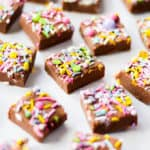 Cubes of milk chocolate microwave fudge with brightly coloured sprinkles on top, side view.