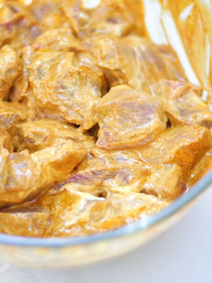 Beef pieces marinating in yoghurt and curry paste for Slow Cooker Beef Curry recipe in glass bowl.