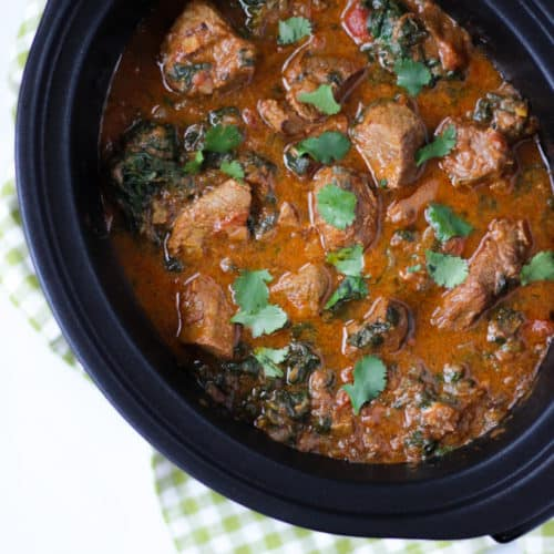 Overhead photo of beef spinach slow cooker curry in black slow cooker with green check cloth.