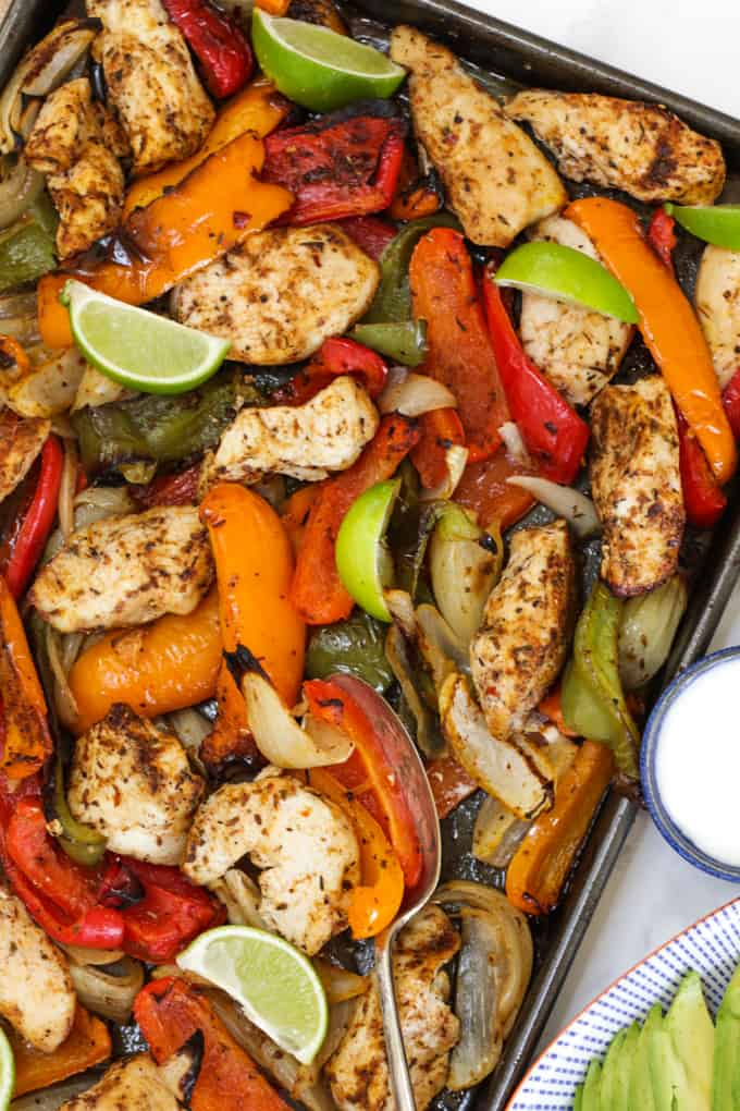 Close up of oven baked chicken fajitas with red peppers, orange peppers and green peppers with lime wedges.
