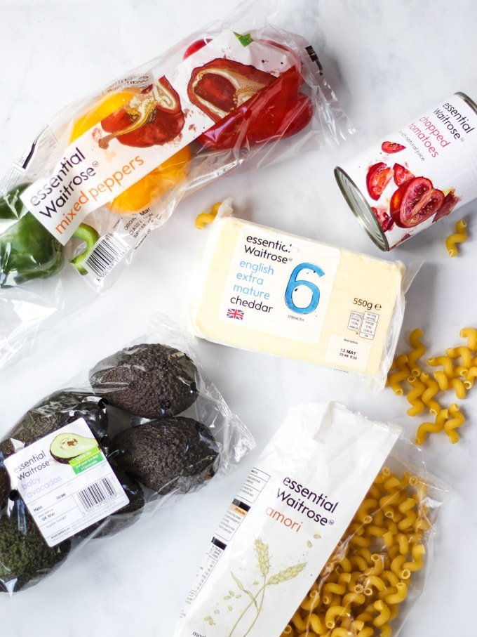 Ingredients from essential Waitrose range for chicken fajita pasta bake including pasta, cheese, avocados, peppers and tomatoes on a white marble background.