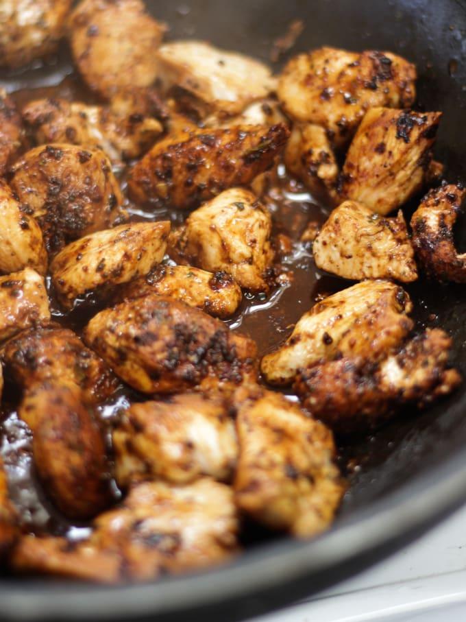 Pieces of chicken with fajita seasoning frying in a black pan for chicken fajita pasta bake.