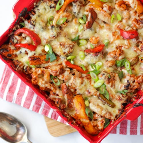Overhead photo of chicken fajita pasta bake with peppers onions and tomatoes in a red square dish on a red and white stripe teatoowl and spoon on a white background.