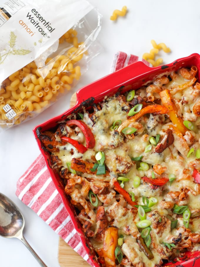 Overhead photo of chicken fajita pasta bake in a red dish with bag of opened pasta and spoon.