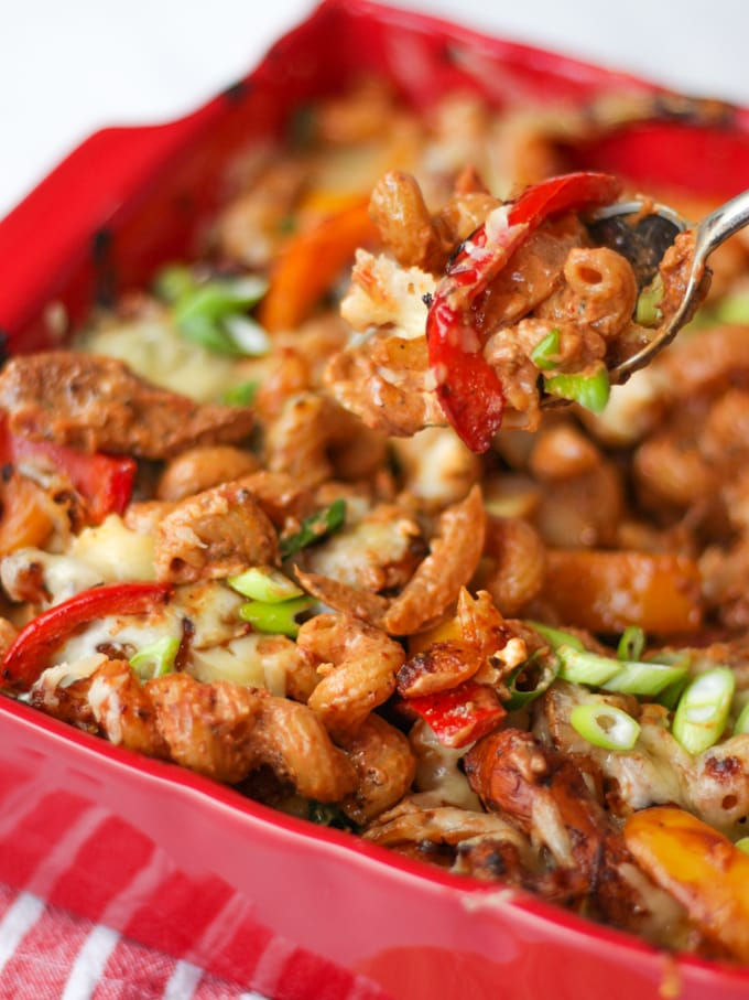 Spoon lifting chicken fajita pasta bake with peppers and scallions spring onions in red dish.
