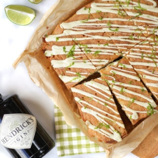 Overhead photo of gin and tonic cake topped with white chocolate and lime with a bottle of Hendricks gin laying next to the cake. With lime wedges and a grey check tea towel.