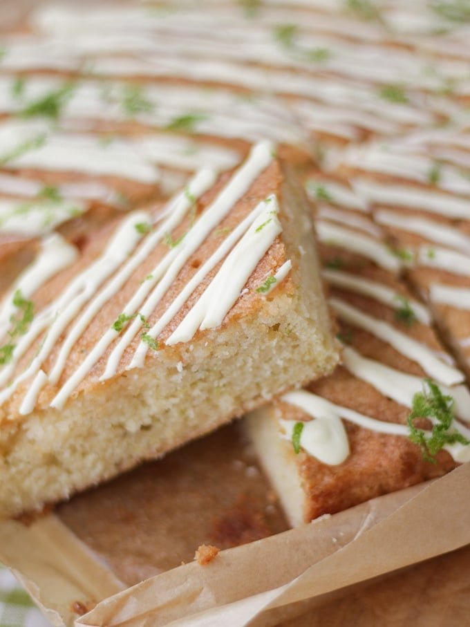 Side view of a gin and tonic cake bar topped with white chocolate drizzle and lime on baking paper.