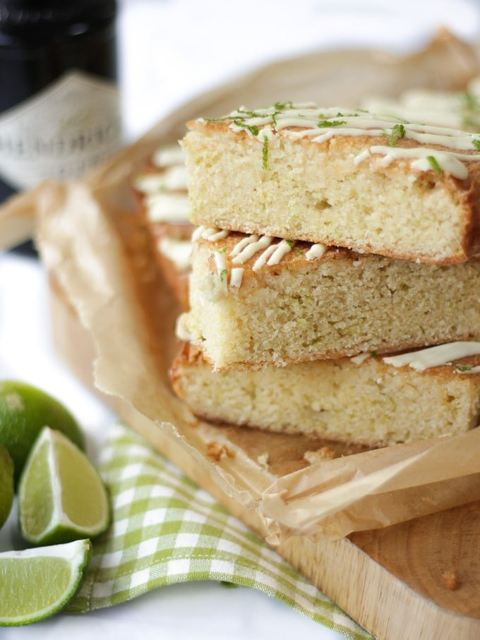 Pile of gin and tonic cake bars with white chocolate drizzle and lime topping with lime wedges and Hendricks gin bottle in the background.