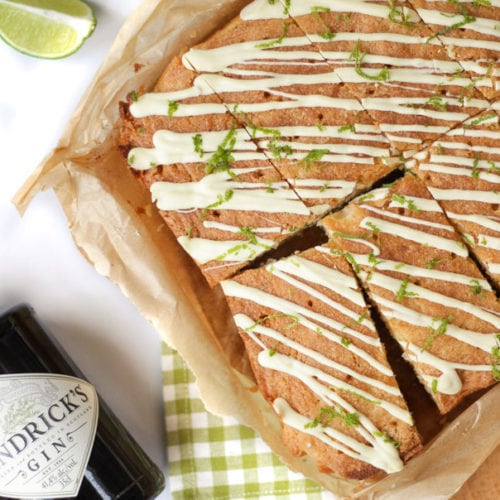 These Gin and Tonic Cake Bars are super simple and delicious. An easy cake packed with gin and tonic flavour, with zesty lime and a crunchy glaze. Based on a lemon drizzle cakestyle recipe, with gin infused syrup and topped with white chocolate.#ginandtonic #cakerecipe #easydessert #tamingtwins
