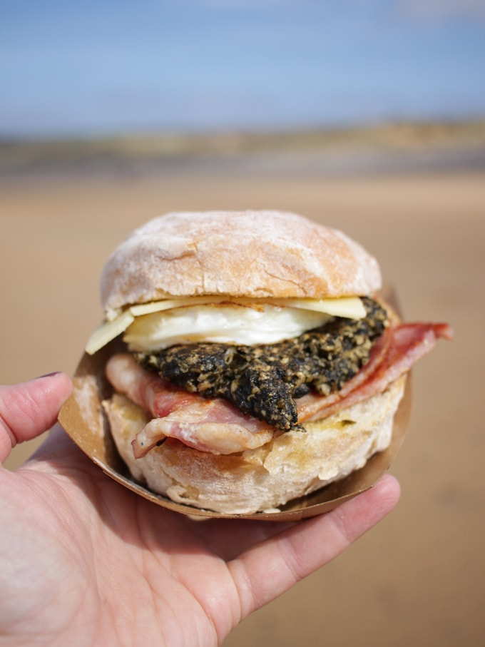 Laverbread bacon egg and cheese bread roll with beach in the background. Cafe More at Freshwater West Beach Car Park,, Nr Castlemartin,, Pembrokeshire, Pembroke Wales SA71 5AH