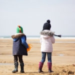 Girl in pink coat and boy in blue coat at Freshwater West Beach Car Park, Nr Castlemartin, Pembrokeshire, Pembroke Wales SA71 5AH