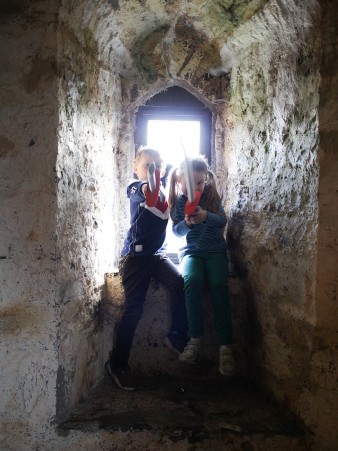 girl and boy in window of Pembroke Castle with toy swords pointing them at the camera.
