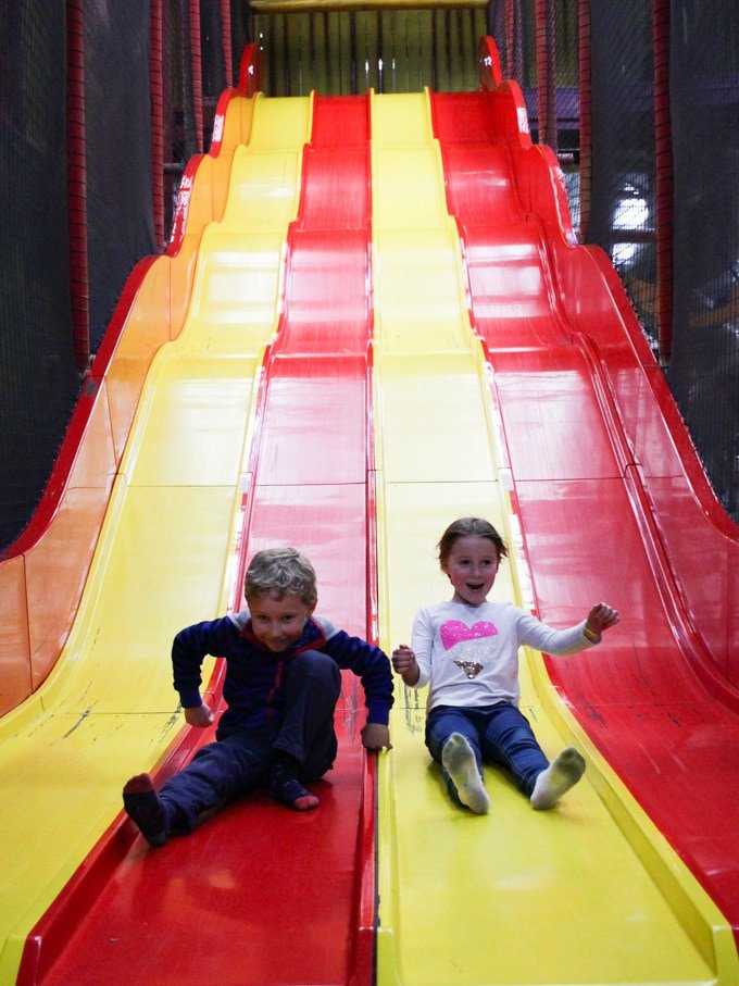 Children in Folly Farm Tenby Pembrokeshire Wales soft play barn area. On big long red and yellow slide.