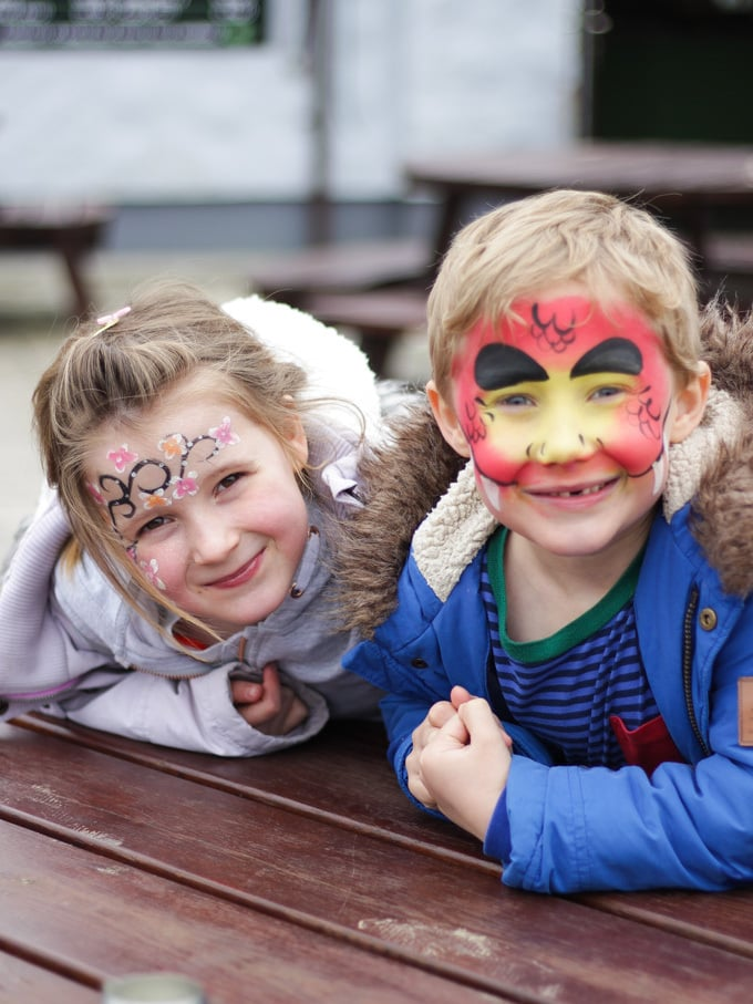 Children with butterfly and snake face paint. Children in Folly Farm Tenby Pembrokeshire Wales soft play barn area.