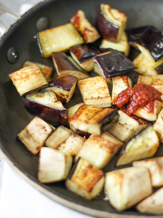 cubes of aubergine for aubergine recipe frying in a black pan with a dollop of Harissa.
