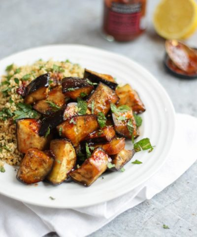 Aubergine recipe of aubergine cubes cooked with Harissa and honey on a white plate with cous cous and grey background.