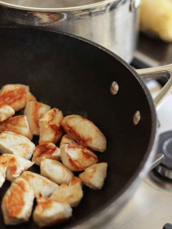 Pieces of chicken fried and golden in a wok on the hob for Chicken Pasta Bake Recipe.