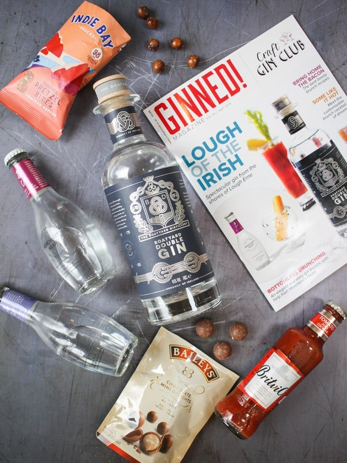 Contents of the May 2018 Craft Gin Club Box laid on a grey background, gin, tonic, britvic tomato juice cocktail