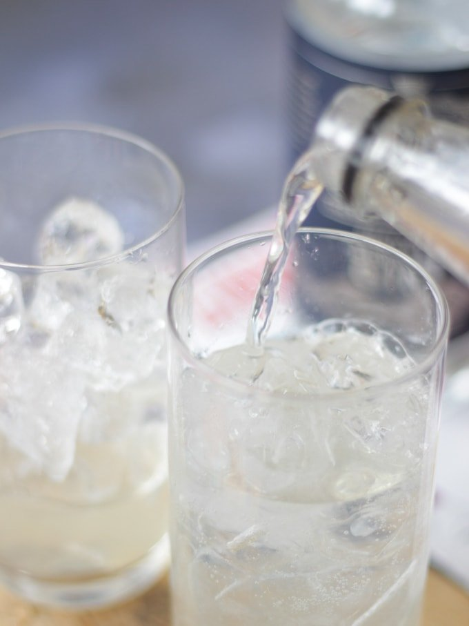 Bottle of soda water pouring into a glass of ice with another glass in background to make gin fizz cocktail recipe