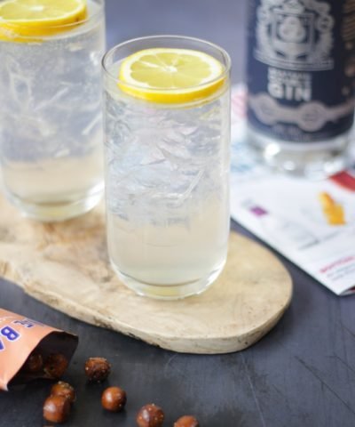 Two highball glasses filled with ice and a slice of lemon on top with gin fizz in the glass.