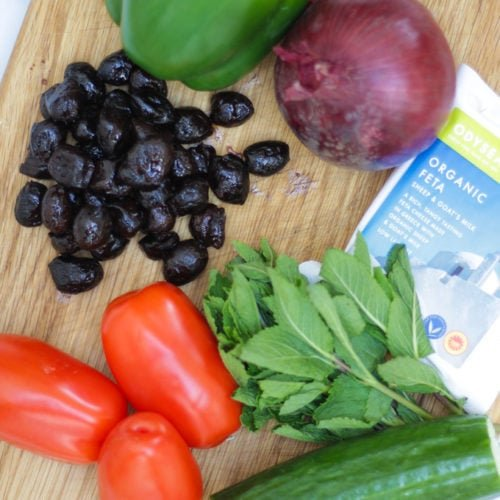 Wooden board with green pepper, red onion, feta, mint, cucumber, tomatoes and olives on for greek salad recipe.