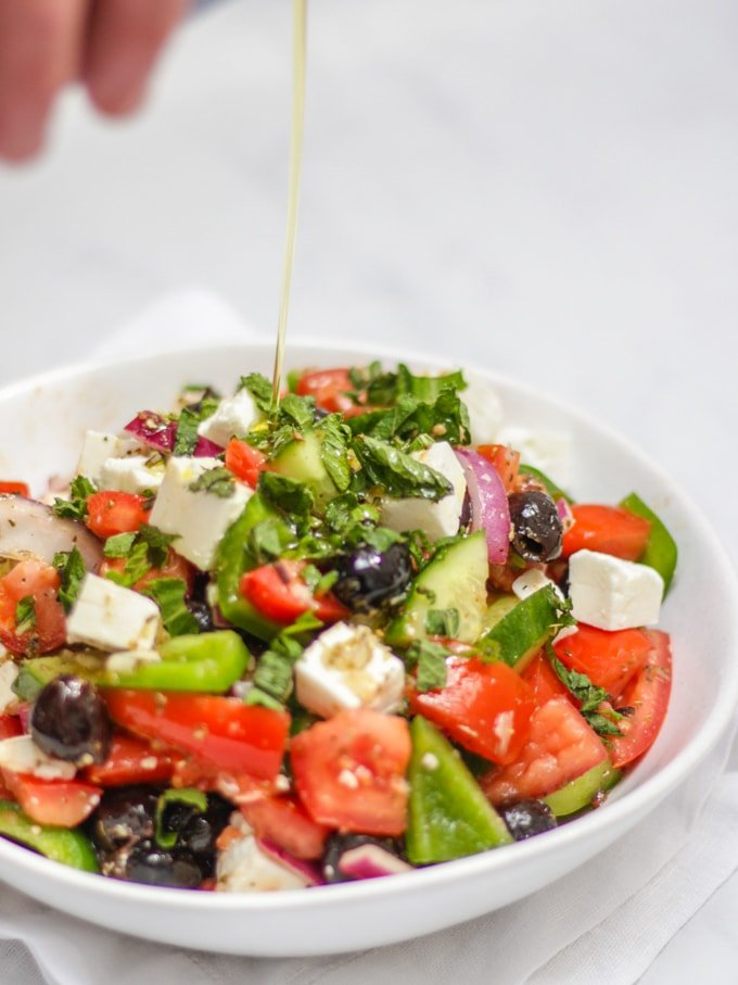 Extra virgin olive oil pouring onto white bowl of greek salad, including green pepper, red onion, feta, mint, cucumber, tomatoes, oregano and olives made with simple easy traditional greek salad recipe.