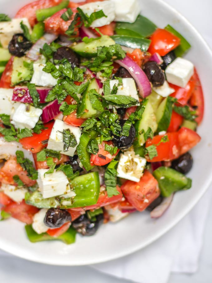 Overhead photo of white bowl of greek salad, including green pepper, red onion, feta, mint, cucumber, tomatoes, oregano and olives made with simple easy traditional greek salad recipe.