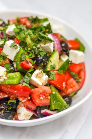 Close up of white bowl of greek salad, including green pepper, red onion, feta, mint, cucumber, tomatoes, oregano and olives made with simple easy traditional greek salad recipe.