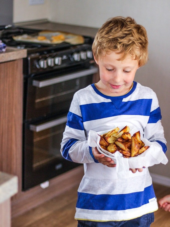 Boy holding a bowl of potato wedges in blue and white strip t shirt. How to make easy peasy Homemade Fish Fingers using our simple recipe. Just four ingredients and supper tasty family meal every time.