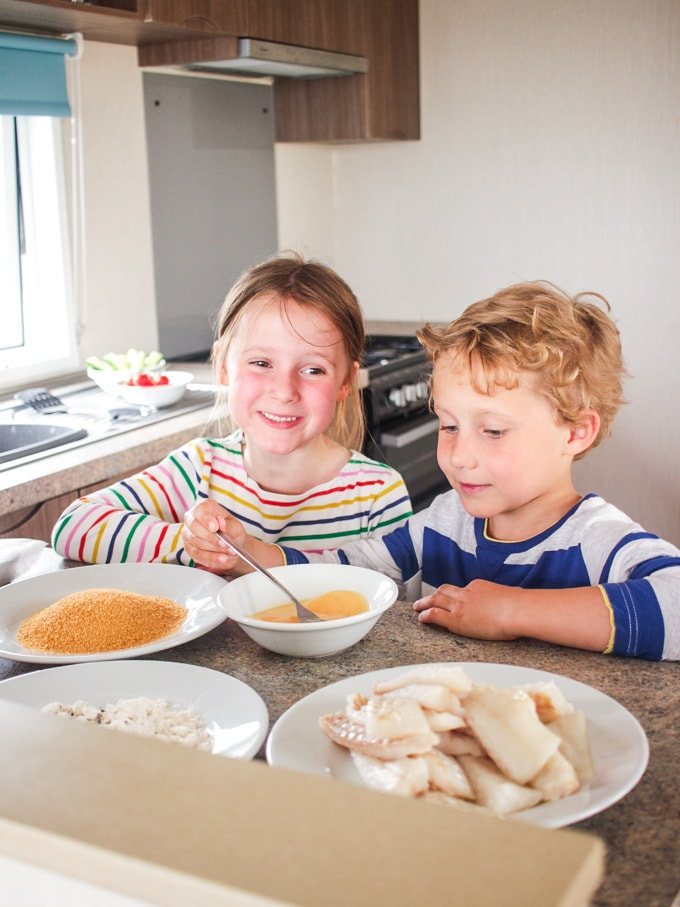 Girl and boy in caravan kitchen making homemade fish fingers. How to make easy peasy Homemade Fish Fingers using our simple recipe. Just four ingredients and supper tasty family meal every time.