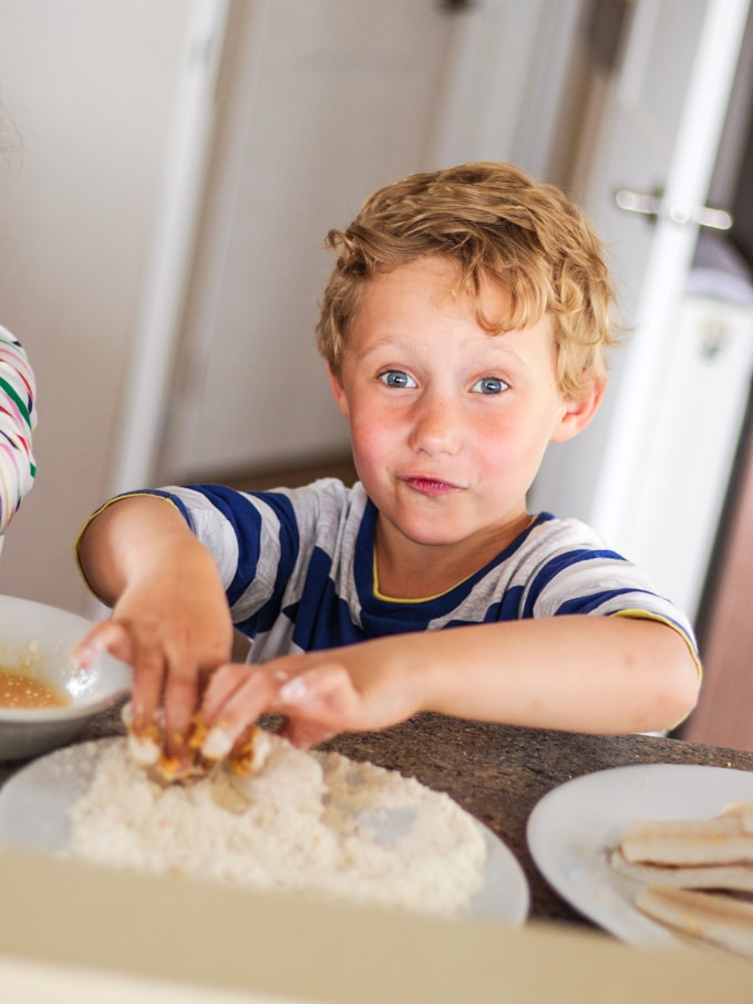 Boy making homemade fishfingers in a caravan kitchen, dipping fish into flour and egg. How to make easy peasy Homemade Fish Fingers using our simple recipe. Just four ingredients and supper tasty family meal every time.