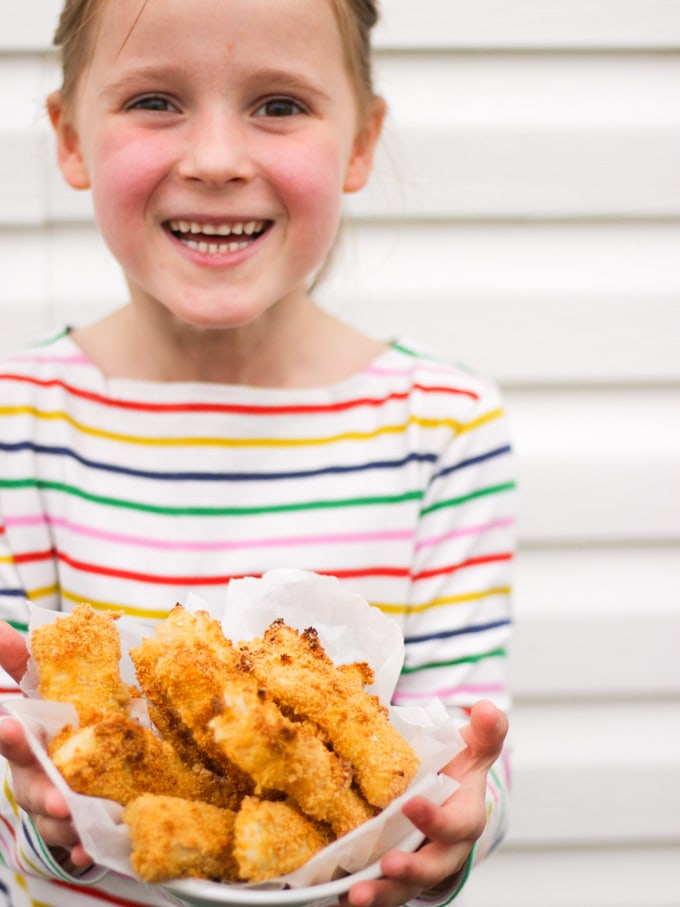 Girl in multi coloured strip t shirt holding a bowl of homemade fishfingers. How to make easy peasy Homemade Fish Fingers using our simple recipe. Just four ingredients and supper tasty family meal every time.