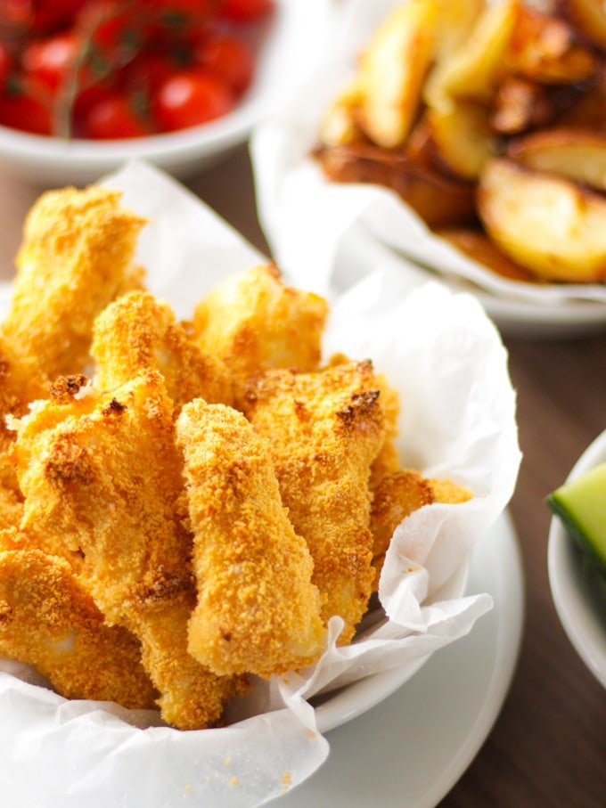 Close up of homemade fish fingers in white bowl with greaseproof paper and potato wedges in the background. How to make easy peasy Homemade Fish Fingers using our simple recipe. Just four ingredients and supper tasty family meal every time.