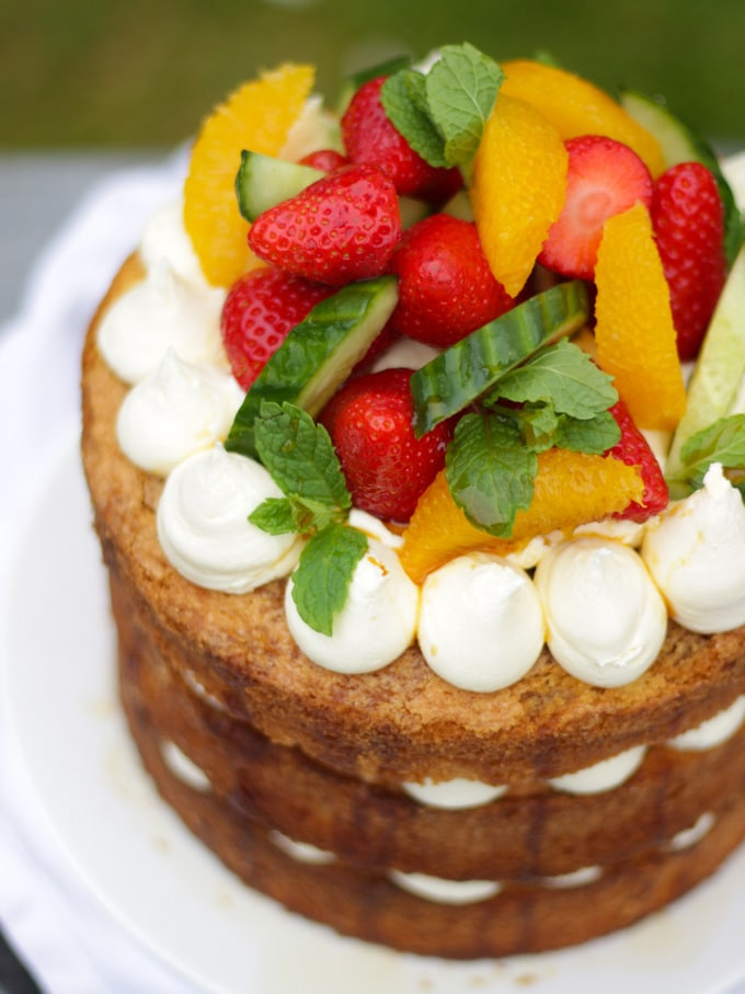 Overhead angled photo of Pimms cake topped with piped buttercream icing, cucumber, strawberries, orange segments and mint on a white plate in a garden with green grass in background to demonstrate pimms cake recipe.