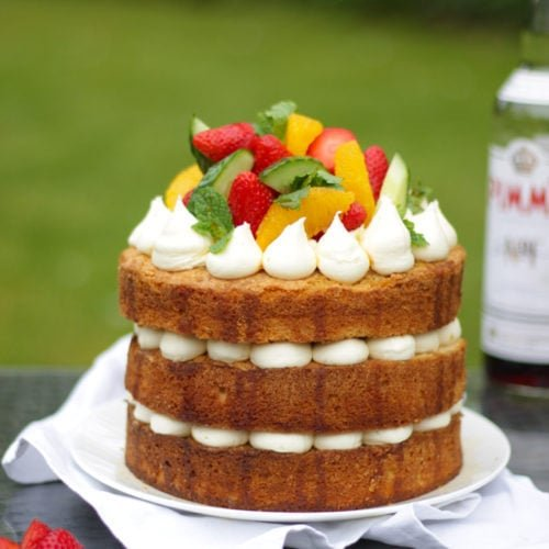 Side photo of Pimms cake topped with piped buttercream icing, cucumber, strawberries, orange segments and mint on a white plate in a garden with green grass in background to demonstrate pimms cake recipe.
