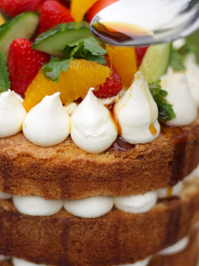 Side photo of Pimms cake with spoon drizzling pimms syrup on cake topped with piped buttercream icing, cucumber, strawberries, orange segments and mint on a white plate in a garden with green grass in background to demonstrate pimms cake recipe.