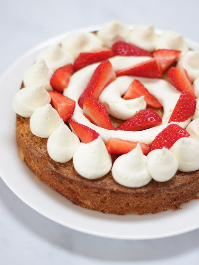 Layer of sponge cake covered with piped white buttercream icing and strawberries for Pimms layer cake recipe.