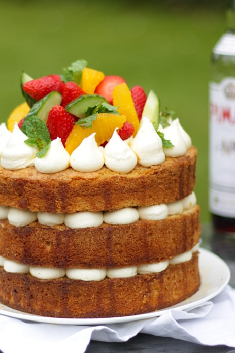 The perfect summer cake recipe! This Pimms Cake recipe is surprising easy, looks impressive and tastes absolutely delicious. Towering with strawberries and drizzled with Pimms syrup, this is a show stopping afternoon tea bake. #pimms #afternoontea #tamingtwins #pimmscake #dessertrecipe #cakerecipe