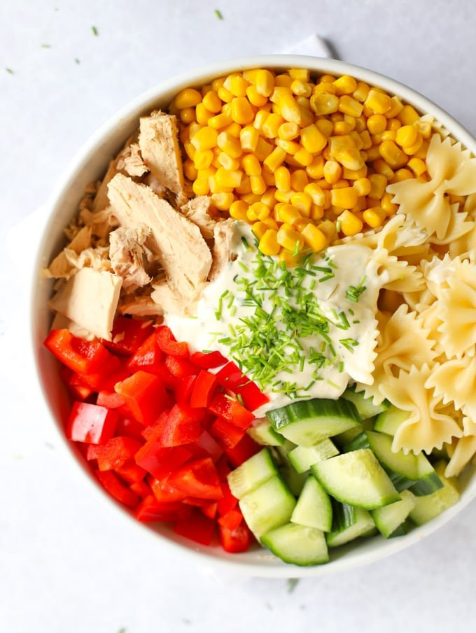 Sweetcorn, tinned fish, pasta, cucumber and peppers with dressing in a bowl