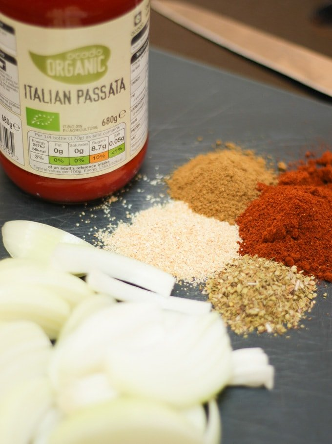 Blue chopping board with chopped onion, herbs and spices and jar of passata, for easy chicken enchiladas recipe which is also slimming world friendly.