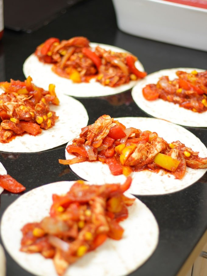 Tortilla wraps laid out on a black work surface with tomato topping ready to be rolled.