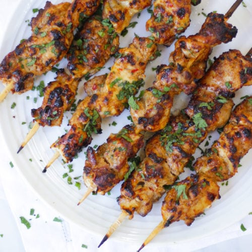 Overhead photo of chicken kebabs on bamboo skewers on white plate.