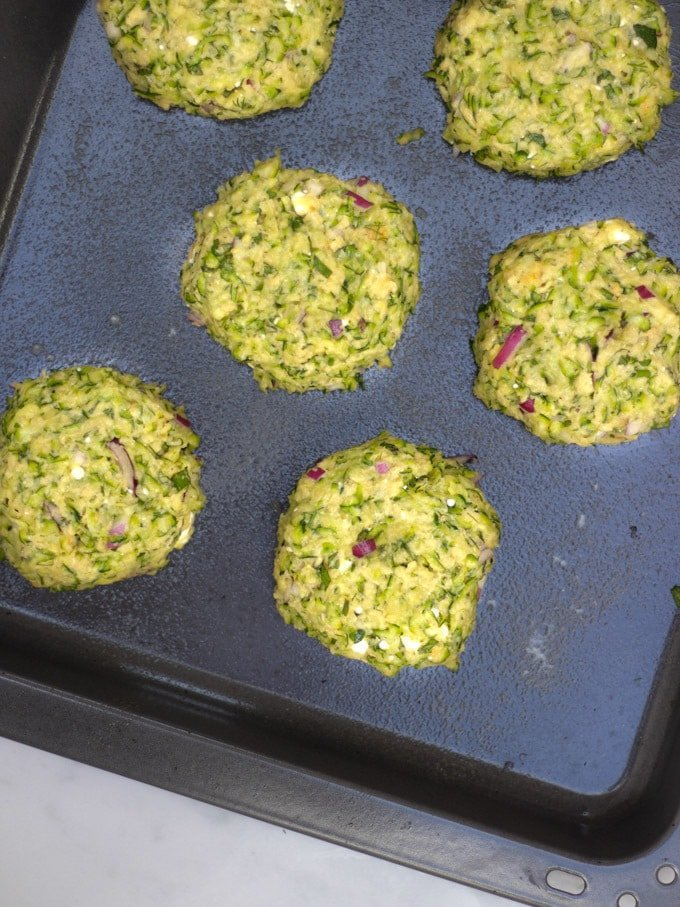 Overhead shot of uncooked patties of courgette fritter recipe batter on a baking sheet.