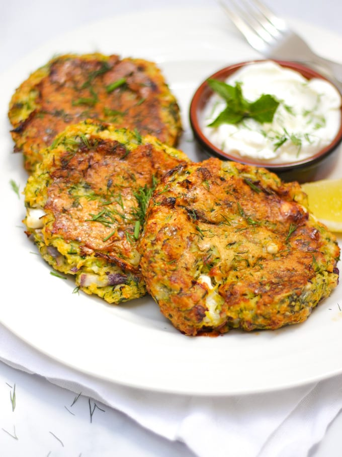 Overhead shot of courgette fritters recipe with 3 fritters on a white plate and a brown pot of yoghurt and dill dip.