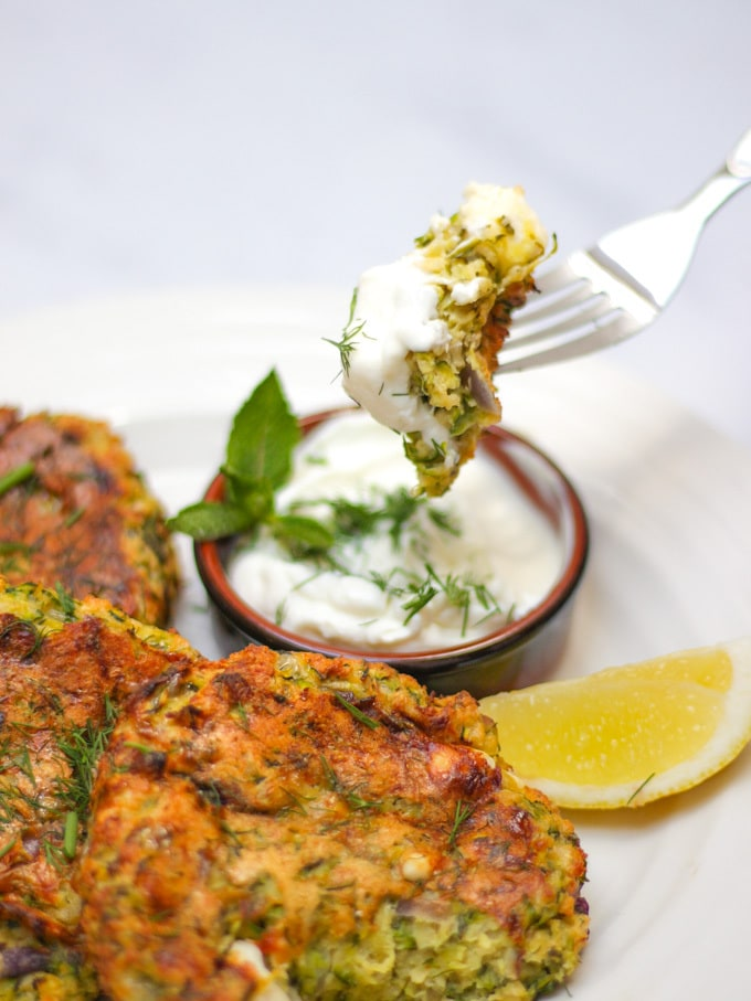Overhead shot of courgette fritters recipe with 3 fritters on a white plate and a brown pot of yoghurt and dill dip with fork pushing in and dipping a mouthful in.